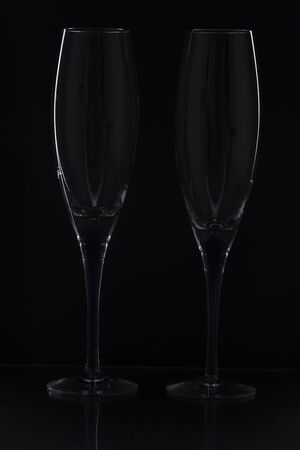 Close up view of contour of a beautiful two slim, tall and elegant champagne glasses isolated on a black background. Beautiful background.