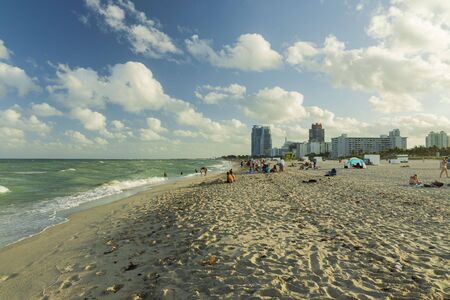 Beautiful landscape view of Miami South Beach coast line. Sand beach, Atlantic Ocean, people and high buildings on blue sky and white clouds background. USA Miami Beach. 24092019. 에디토리얼