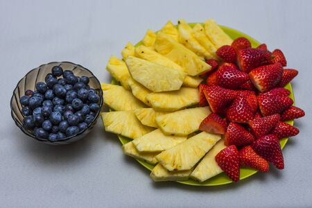 Close up view of colorful berries. Blueberries, sliced pineapple, strawberries.