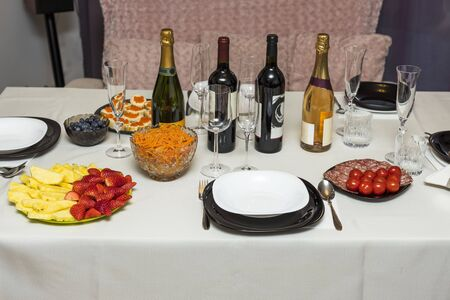 Close up view of served table with white cloth. Colorful fruits and vegetables, salads and snacks. Alcohol and alcohol free bottles. 스톡 콘텐츠