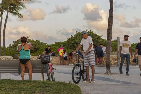 Beautiful tropical landscape view. People changing after visiting beach and some people with bicycles on green trees and pale blue sky with white clouds background. Miami South Beach. USA 24092019.