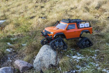 View of radio controlled model racing car on off-road background. Toys with remote control. Free time. Children and adults concept.