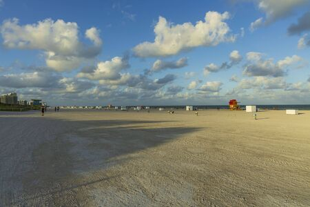 Beautiful landscape view of Miami South Beach coast line. Sand beach, Atlantic Ocean, people and high buildings on blue sky and white clouds background. USA Miami Beach.
