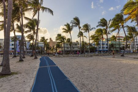 Gorgeous landscape view of rubber coated track on sand beach on green trees and blue sky with white clouds background. Tourism concept. Miami South Beach, Florida. USA 24092019.