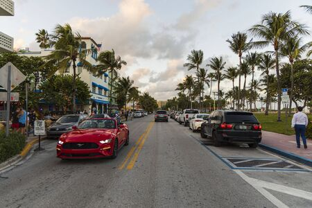 Beautiful landscape view of street of Miami Beach. White buildings, cars and palm trees on both sides of asphalt road on blue sky and white clouds background. USA Miami South Beach. 24092019.