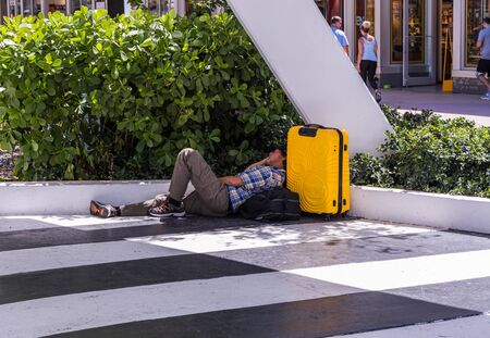 View of tired man with yellow bag sleeping on floor near green bushes on walking street. Miami USA 24092019.