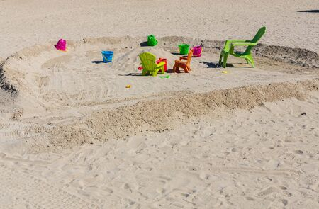 Cute view of colorful sand toys on sandy beach. Family tourism concept.