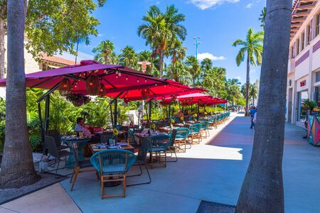 Beautiful landscape view of outdoor cafe. Blue chairs under red umbrellas on green trees and blue sky background. Miami USA 24092019. 에디토리얼