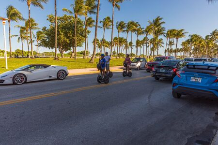 View of tourists driving on segways on beautiful summer day. Road and green palm trees on blue sky background. USA Miami South Beach. 24/09/2019.
