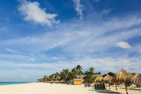 Beautiful view of white sand beach with sun umbrellas and sunbeds. Eagle beach. Aruba island. 写真素材
