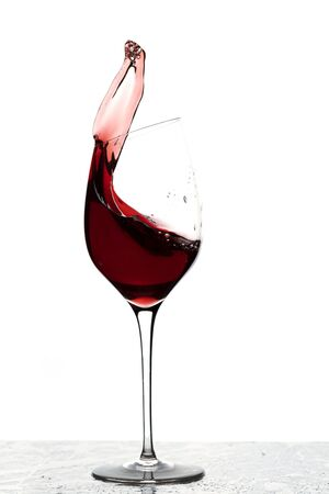 Close up view of splashing red wine in glass isolated on white background. 版權商用圖片