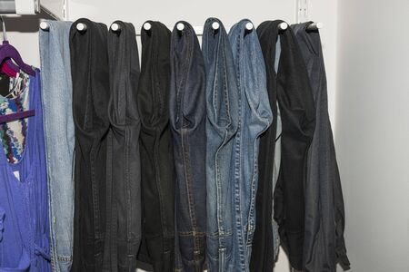 Close up view of interior of built-in wardrobe. Blue and black jeans on white hangers. Cloth organizer.
