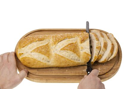 Close up view of partially sliced loaf of bread on wooden cutting board with bread knife. Food and health concept beautiful backgrounds.
