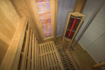 Infrared sauna interior close up view. Wooden walls and bench, ceramic heaters. Healthy lifestyle concept.