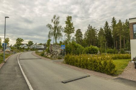 View of speed bump on village street road. Landscape view background. Europe Sweden