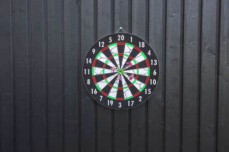 View of dartboard with missiles on black wooden wall isolated. Sport and hobby concept. Banco de Imagens