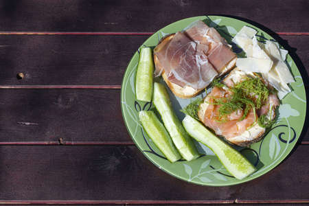 Close up view of plate with two sandwiches, chees and cucumber on wooden background. Healthy eating concept.