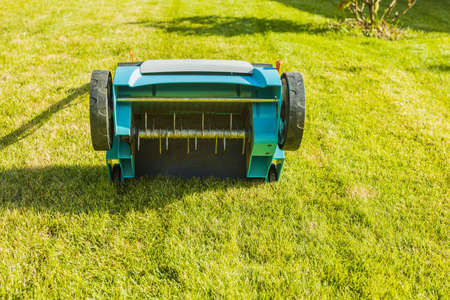 Close up view of electric lawn aerator on green grass isolated. Garden machines concept.