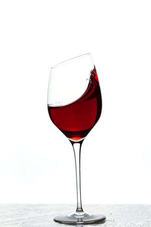 Close up view of splashing red wine in glass isolated on white background. 写真素材