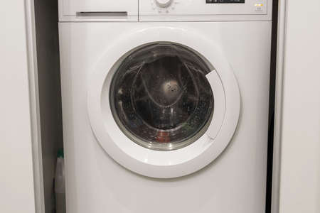 Close up view of laundry spinning in washing machine isolated. Home appliances concept.