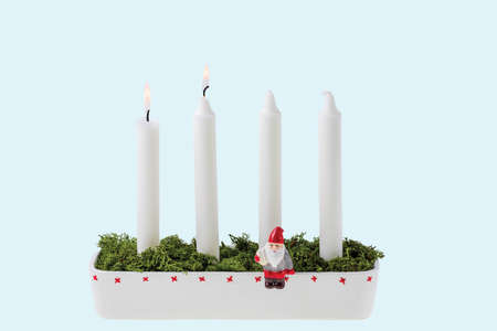 Close up view of traditional advent candlestick with one lighted candle symbolizing second advent isolated on blue background.