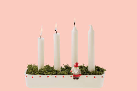 View of traditional advent candlestick with one lighted candle symbolizing third advent isolated on pink background.