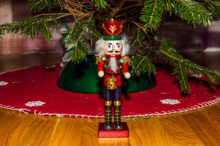 Close up view of cute Nutcracker figure with green Christmas tree. Christmas holidays concept.