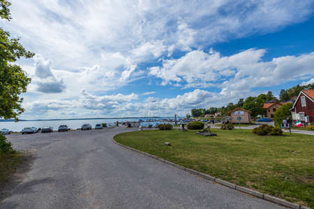 Gorgeous coast line landscape view. Buildings and road to parking place on Baltic sea water surface and blue sky with white clouds background. Sweden. Kolmarden. 08.28.2020. Editorial