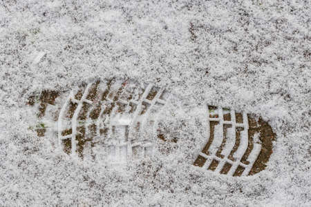 Close up view of shoe print on snowy asphalt road. Winter season concept.
