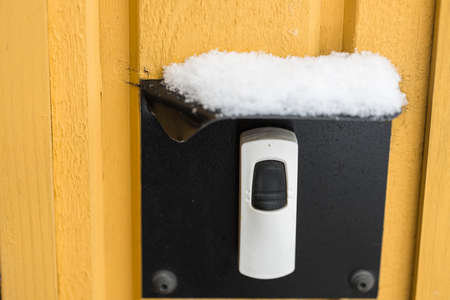 Close up view of snowy protected cover over electric doorbell button. Winter season concept. Standard-Bild