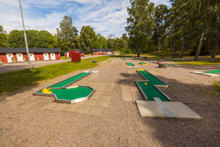 Beautiful landscape view of summer country landscape view. Mini golf court and red houses on green trees and blue sky with white clouds background. Sweden. Europe.