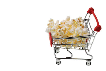Close up view of popcorn in shopping cart on white background isolated. Unhealthy food concept.