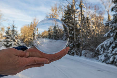 Close up macro view of hand holding crystal ball with image of winter natural landscape. Sweden. 版權商用圖片