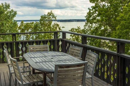 Overview of outdoor wooden veranda around private house with gorgeous landscape on Baltic sea. Beautiful backgrounds of nature. Sweden.