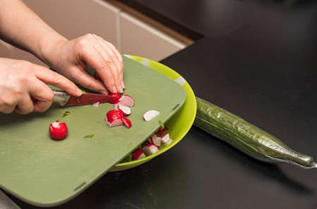 View of female cutting radish for green salad. Healthy eating concept. Stok Fotoğraf