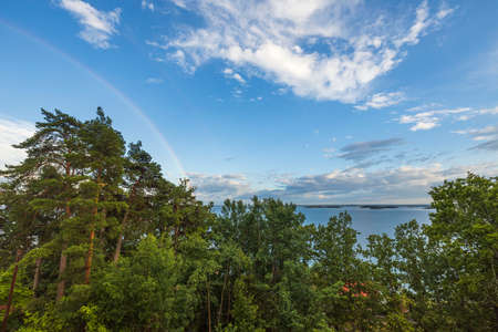 Beautiful view of tops of green trees on blue sky with a rainbow after rain on background Baltic sea. Sweden. Stok Fotoğraf