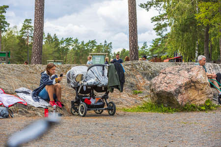 View of young woman sitting near baby sleeping in baby carriage in park. Kolmorden, Sweden. 09.28.2020. Editöryel