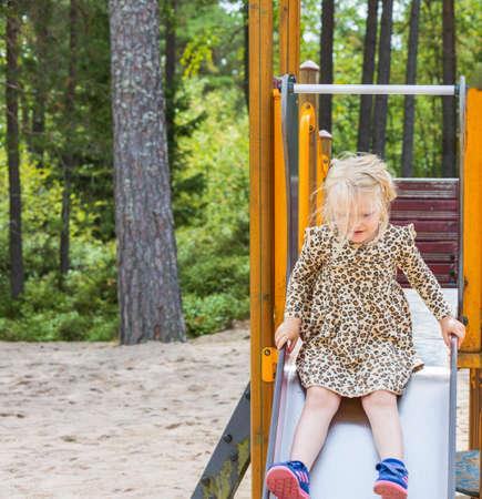 Close up view of girl playing on kids slide in park. Kolmorden, Sweden. 09.28.2020.
