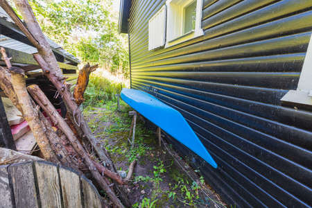 Close up view of blue kayak parked near dark house wall. Sweden.