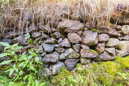 Close up view of natural stone wall on natural landscape.