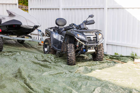 Close up view of off-road vehicle with water scooter with a scooter on trailer on white fence background.