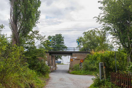 Beautiful landscape view. Small road passing under bridge. Green trees on cloudy sky background. Stok Fotoğraf