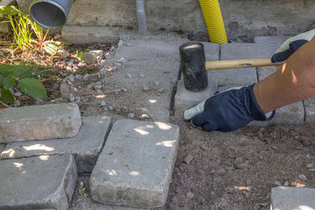 Close up view of man laying paving slabs. Sweden.