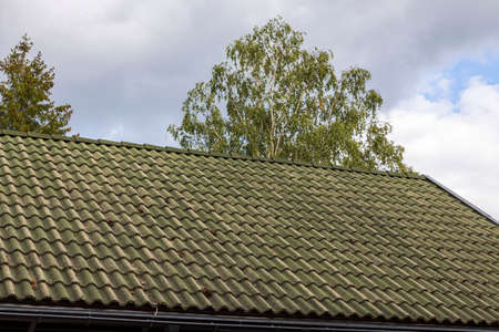 Beautiful view of dark gray old tiled roof on sky background. Beautiful backgrounds.