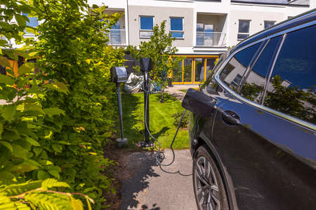 Close up view of parked vehicle connnected to charging station. Sweden Stok Fotoğraf