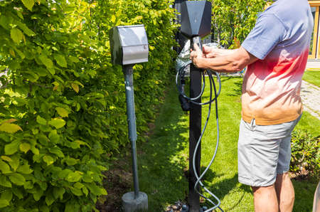 Close up view of man connecting charging cable to charging station for electric car. Sweden.