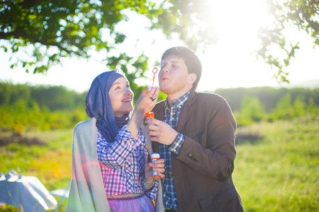 supercharger: Young couple play together with bubble blower Stock Photo