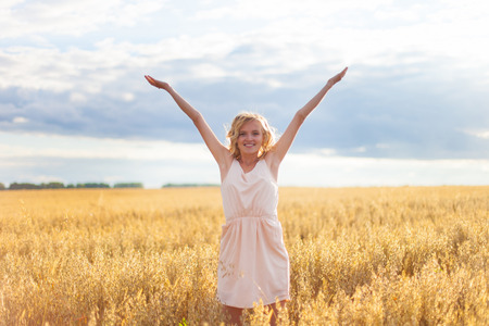 outstretched: Woman in Wheat Field With Arms Outstretched Stock Photo
