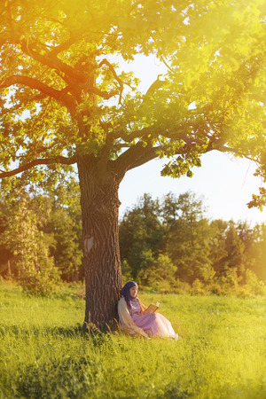 petite fille musulmane: Femme musulmane de lire un livre sous le sapin Banque d'images