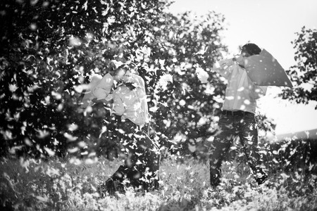 pillow fight: Couple having a pillow fight on field